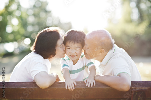 Chinese grandparents kissing grandson