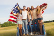 Friends holding American flag on back of truck