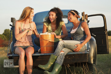 Laughing friends churning ice cream in back of truck