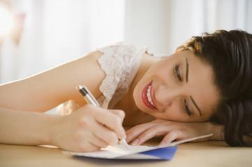 Mixed race woman writing on birthday card