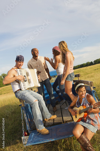 Friends playing musical instruments on back of truck