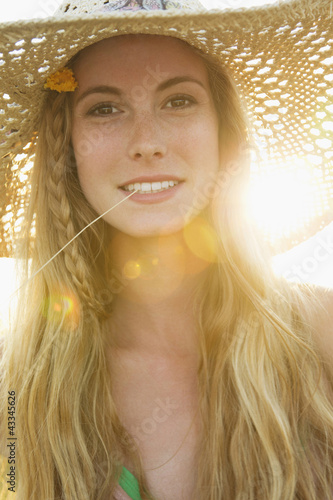 Caucasian woman in hat biting weed stalk