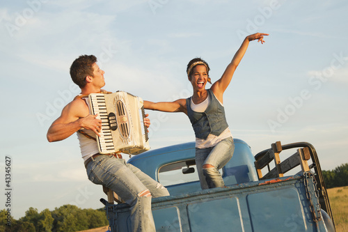 Man playing accordion for girlfriend in back of truck