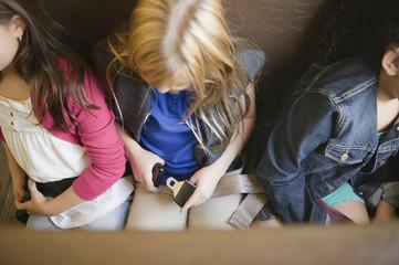 Children buckling seat belts on school bus