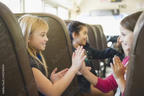 Children playing while riding school bus