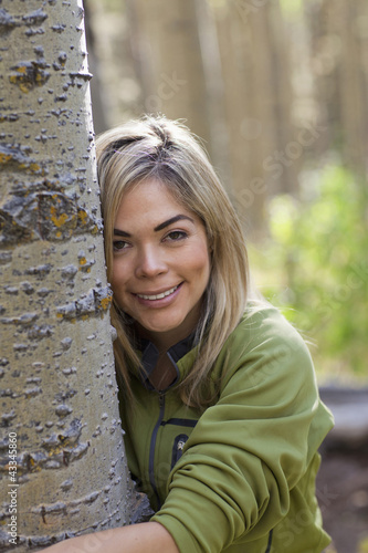 Hispanic woman hugging tree in forest