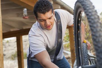 Hispanic man repairing his bicycle