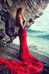 The beautiful red-haired girl poses on a sandy beach