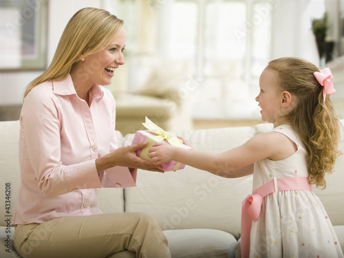 Caucasian daughter giving mother a gift