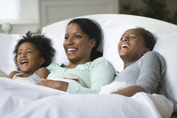 Mother and daughters watching television in bed