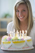 Caucasian teenage girl sitting with birthday cake