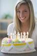Caucasian teenage girl sitting with birthday cake