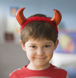 Smiling Caucasian boy in devil costume
