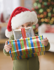 Caucasian boy in Santa hat holding gifts