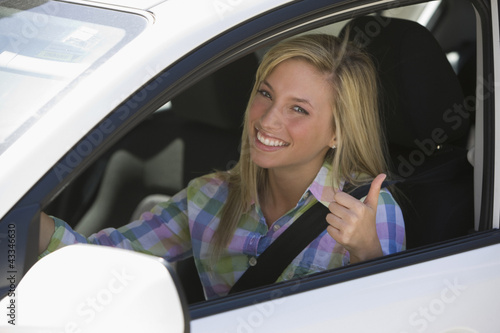 Caucasian teenage girl driving car giving thumbs up