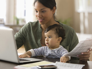 Mixed race mother working on computer with baby boy on her lap