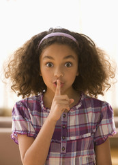Mixed race girl making shhh gesture
