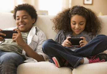 Brother and sister playing video games on sofa