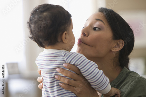 Mixed race mother kissing baby boy