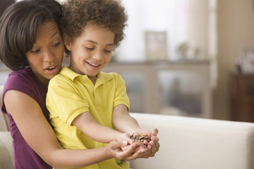 Mother and son holding handful of coins