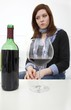 Woman drinking wine (focus on bottle)