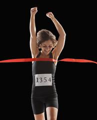 Caucasian woman running across race finish line