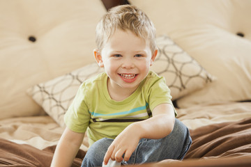 Smiling Caucasian boy sitting on bed