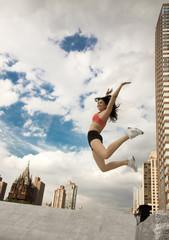 Woman in sportswear jumping on roof