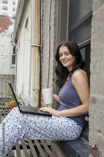 Woman using laptop on fire escape