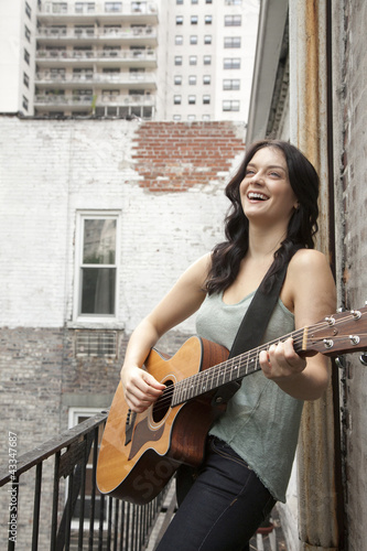 Woman playing guitar on fire escape
