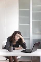 Bored businesswoman sitting at desk