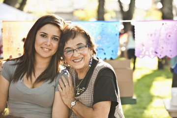 Smiling Hispanic grandmother and granddaughter