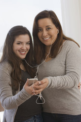 Chilean mother and daughter listening to mp3 player