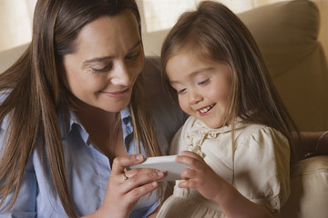 Chilean mother showing cell phone to daughter