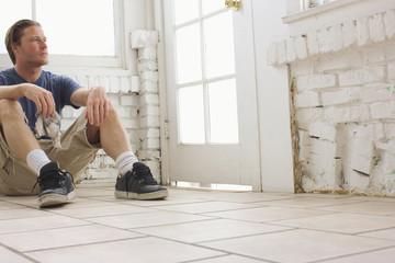 Caucasian man sitting on floor