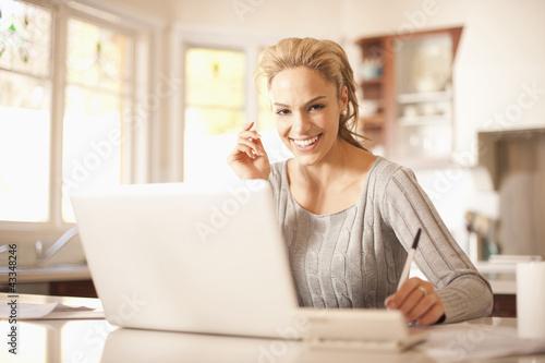 Hispanic woman using laptop in kitchen