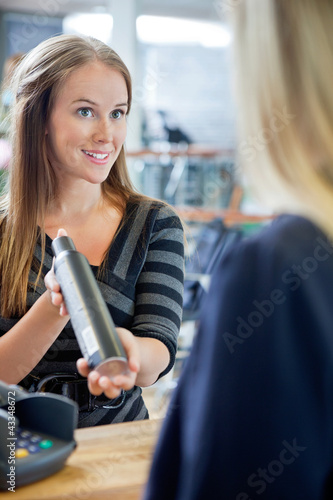 Hairstylist Showing Hair Product To Customer