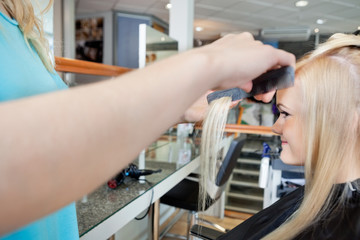 Hairdresser Combing Hair Of Woman