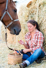 Girl and her horse resting near a haystack