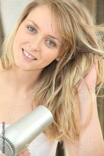 Blonde woman using a hairdryer