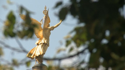 Angel of Victory behind some green leafs