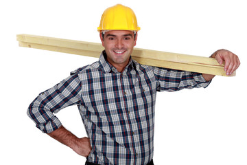 Cheerful carpenter carrying timber