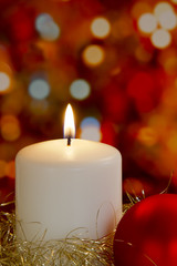 Cream candle, gold tinsel, bauble and blurred light background