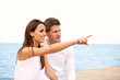Beautiful Woman with Her Boyfriend Pointing Toward the Sea