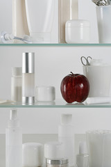 Medicine cabinet full of skincare products and a red apple