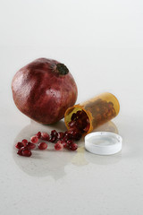 Pill bottle full of pomegranate seeds next to pomegranate