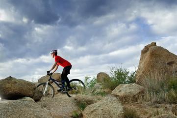 Caucasian man riding mountain bike in remote area