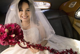 Hispanic bride sitting with bouquet in car