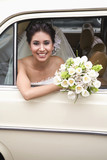 Hispanic bride sitting with bouquet in back of car