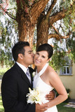 Hispanic groom kissing bride